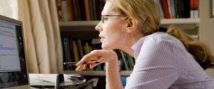 Une femme lit son écran avec des lunettes